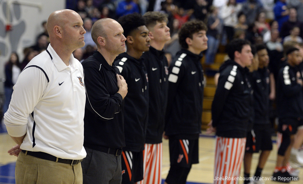 . Vaca High head coach Duane Kamman stands with his players as the national anthem is played before tipoff of their showdown with their rivals, Will C. Wood Thursday at Wood.