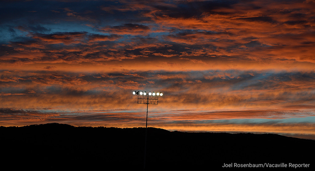 . The vibrant colors of the setting sun is reflected in clouds above Tom Zunino Stadium before kickoff of the Bulldogs game against Pittsburg High School.