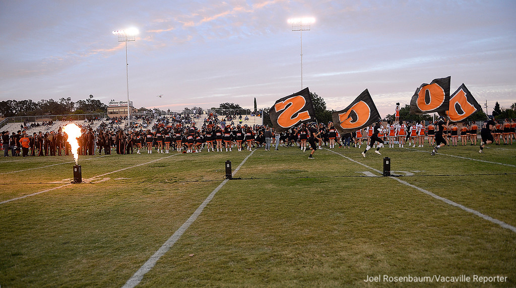 . Members of the Vacaville High junior varsity football team carry the Bulldog flags before kickoff of the varsity game against Pittsburg High Friday at Tom Zunino Stadium.