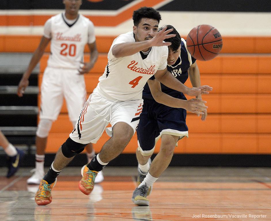 . Vacaville High\'s Issac Zulueta chases down a loose ball as Napa High\'s Tatsu Nakaima trails behind during the second quarter of the Bulldogs league victory Tuesday at Vaca High.