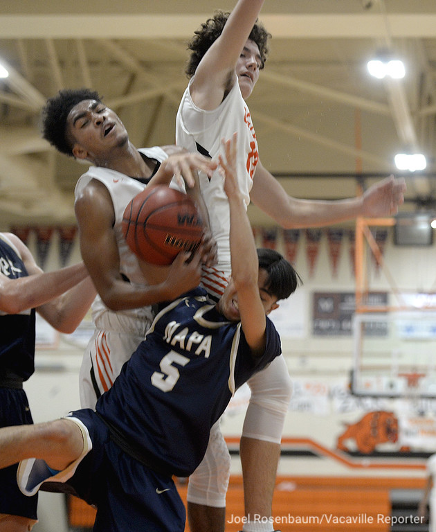 . Vaca High\'s Jordan Adams (left) and Joey Murga collide with Napa High\'s Tatsu Nakaima as they fight for possession of loose ball during the second quarter of the Bulldogs\' league victory.