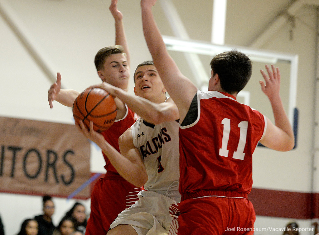 . Vacaville Christian High\'s Adam Grabowski drives between Alpha Charter double team of Jacob Thompson (left) and AJ Comstock during the first quarter of the Falcons\' 62-38 victory in the first round of the CIF Sac Joaquin Section Division VI Championships Friday at Vaca Christian High.