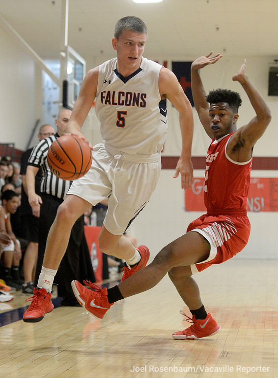 . Vacaville Christian High\'s Adam Grabowski leaps over Alpha Charter\'s Jamil Manning as he drives up court during the first quarter of the Falcons first round game in the CIF Sac Joaquin Section Division VI Championships Friday at Vaca Christian High.