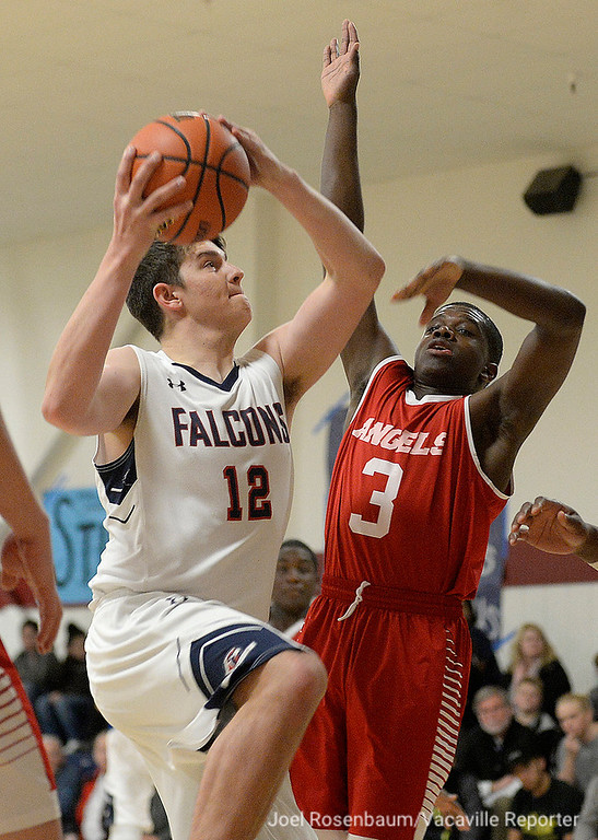 . Vacaville Christian\'s Tyler Kenyon drives to the basket as Alpha Charter\'s Rahmel Hinkle pressures during the first quarter of the Falcons\' 62-38 victory over Alpha Charter High School in the first round of the CIF Sac Joaquin Section Division VI Championships Friday at Vaca Christian High.