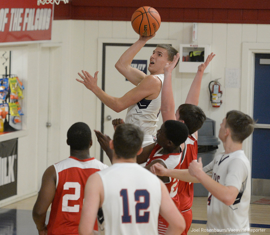. Vacaville Christian High\'s Adam Grabowski drives to the basket over a several defenders from Alpha Charter High School during the second quarter of the Falcons\' 62-38 victory in the first round of the CIF Sac Joaquin Section Division VI Championships Friday at Vaca Christian High.