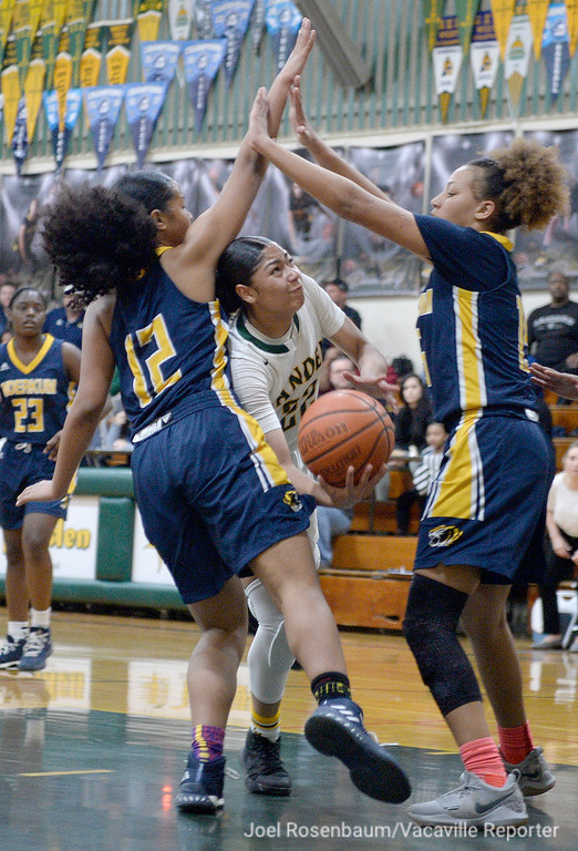 . Vanden\'s Myli Martinez fights through the double team of Inderkum\'s Sidney Richards (left) and Joe\'l Benoit as drives to the basket during the fourth quarter of the Vikings\' 71-66 overtime victory in the first round of the Sac Joaquin Section Division II Championships.