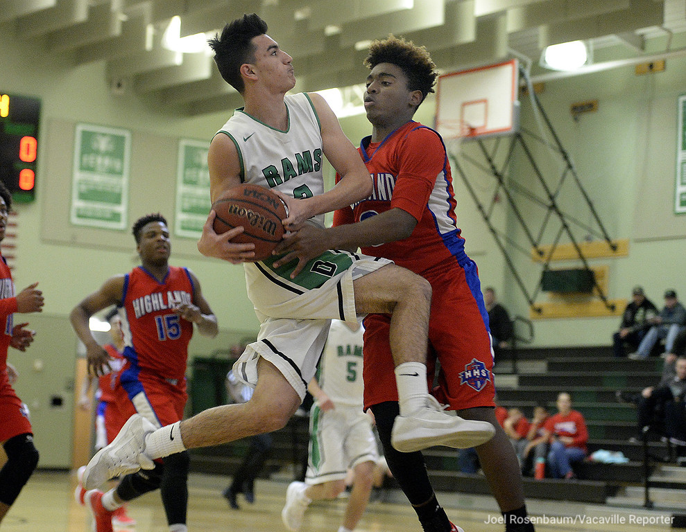 . Dixon High\'s Anthony Hatfield drives to the bucket through the pressure from Highland High School\'s Gerald Davis during the first quarter of the Rams 81-44 rout of the Scots in the first round of the 2018 CIF Sac Joaquin Section Division IV Championships Wednesday at Dixon High School.