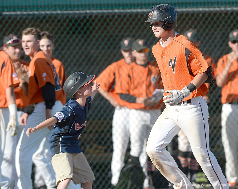. Vacaville High School bat boy, Jonovan Karuzas welcomes home Bryce Begell after his seventh inning home run.