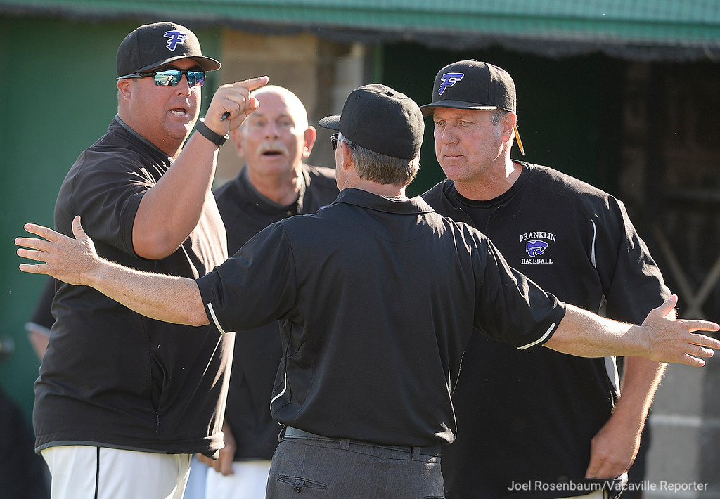 . Members of the Franklin High School coaching staff argue with the umpire after they called one of their players out at home during the sixth inning.