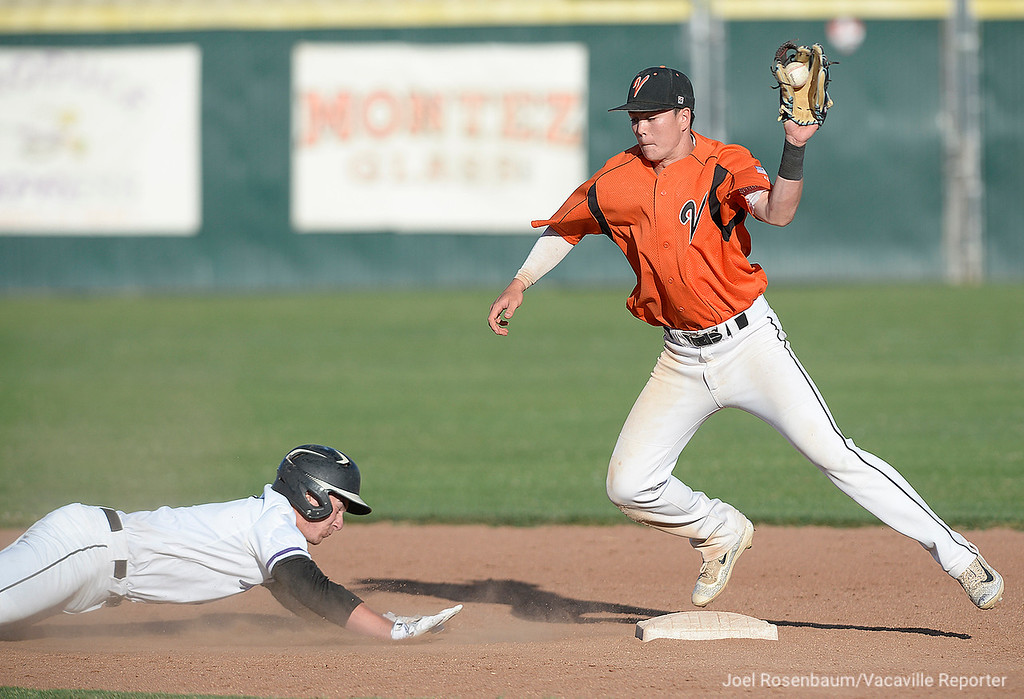. Vacaville shortstop,  Bryce Begell catches a throw from catcher, Cole Elvis on a attempted pick off of Franklin High\'s Ty Tobey at second base during the seventh inning.