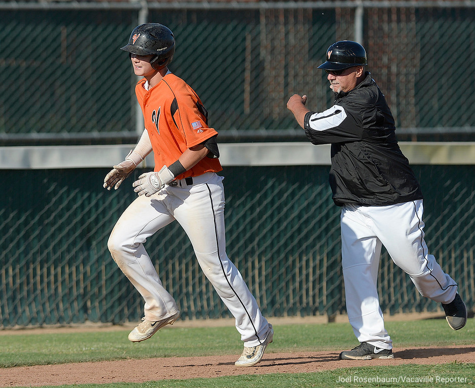. Vacaville High\'s Bryce Begell is waved home by head coach, Stu Calry as he rounds third base after his seventh inning solo home run.