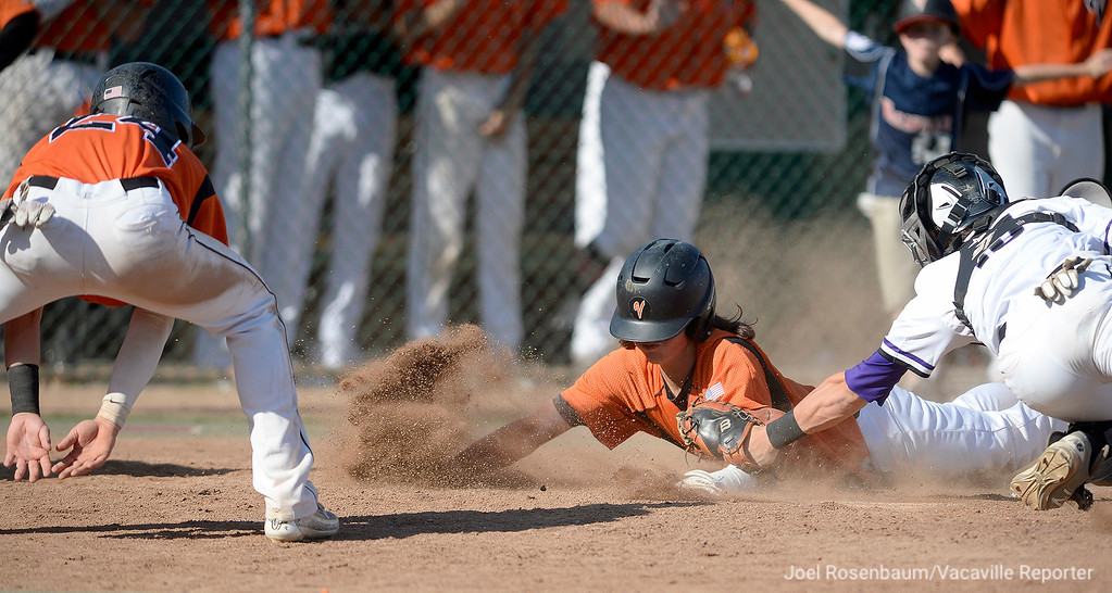 . Vacaville High\'s Devereaux Harrison slides home past the tag attempt Franklin High catcher, Carson Stevens with the Bulldogs\' third run of the ball game during the fifth inning of the \'Dogs 11-2 rout of Franklin High School in the elimination round of the 2018 CIF Sac Joaquin Section Division I Championships Tuesday at Union Stadium on the campus of Sacramento City College. With the victory they advance to play Jesuit High School Thursday at Sac City College.