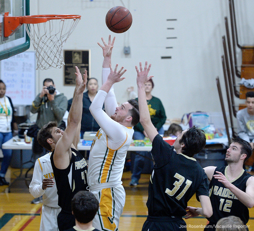 . Vanden\'s Aaron Kelly drives basket through the double team of Rio Americano\'s Chris Sheehy (left) and Jonah Roth during first quarter in the quarterfinals of the 2018 CIF Sac Joaquin Section Division III Championships Friday at James Boyd Gymnasium.