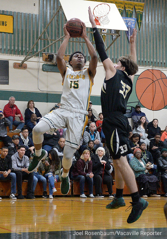 . Vanden High\'s Teiano Hardee drives to the basket under pressure from Rio Americano Highs\' Kyle Astleford during the third quarter of their upset loss in the quarterfinals of the 2018 CIF Sac Joaquin Section Division IV Championships Friday at James Boyd Gymnasium.