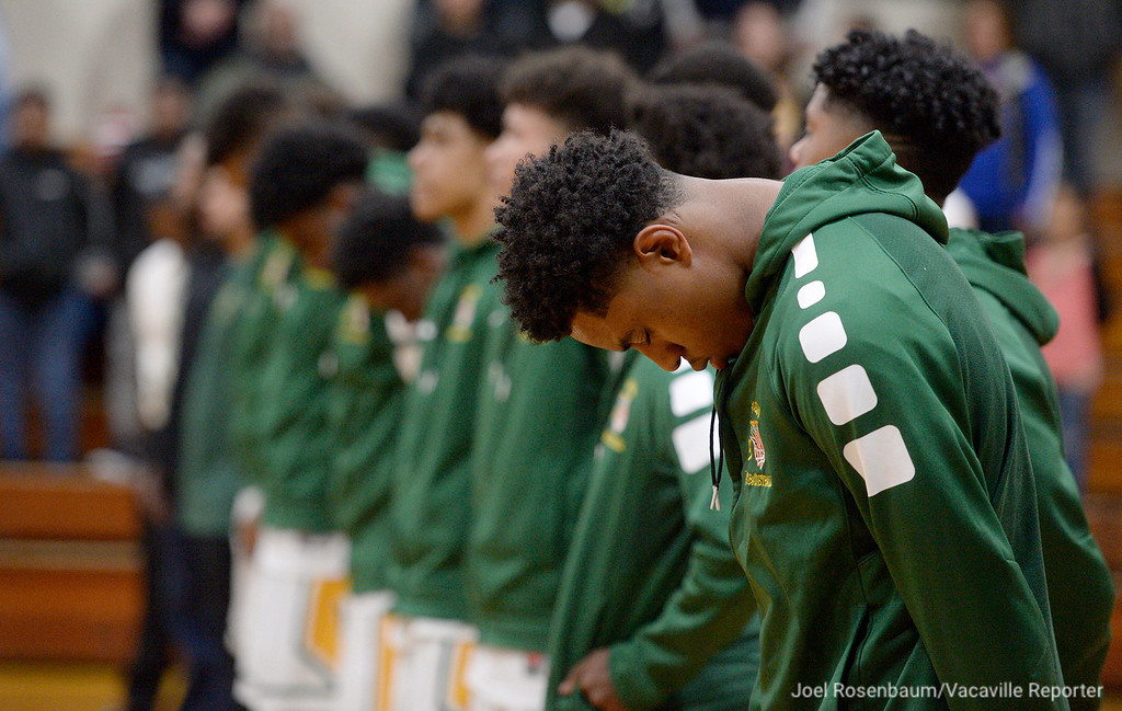 . Members of the Vanden High boys basketball team stand together as the national anthem is sung before tip off of their second round match up against Rio Americano High in the 2018 CIF Sac Joaquin Section Division III Championships.