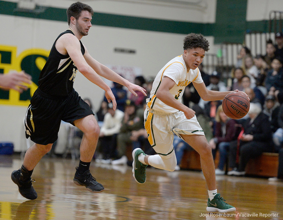 . Vanden\'s Johnathan Cobbs drives past Rio Americano\'s Matt Dixon on a fast break during the second quarter of the  Vikings\' upset loss to the Raiders in the quarterfinals of the 2018 CIF Sac Joaquin Section Division III Championships Friday at James Boyd Gymnasium.