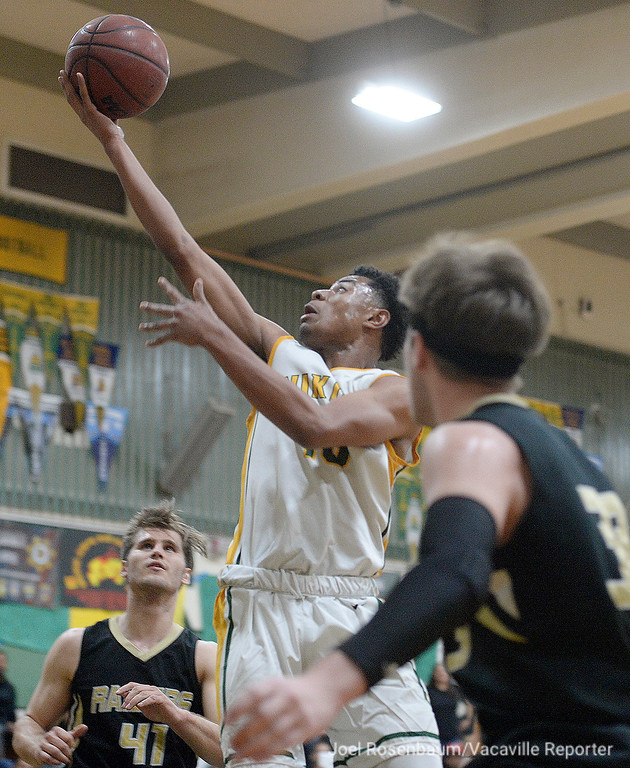 . Vanden High\'s Teiano Hardee drives to the basket between  Rio Americano Highs\' Chris Sheehy (left) and Kyle Astleford during the third quarter of their upset loss in the quarterfinals of the 2018 CIF Sac Joaquin Section Division IV Championships Friday at James Boyd Gymnasium.