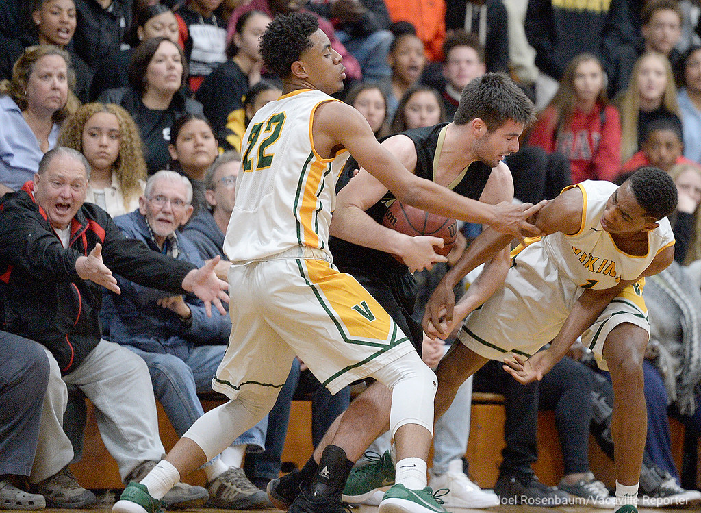 . Vanden HIgh\'s Kunim Dwumfuoh and Marquis Davison-Holloway press Rio Americano High\'s Matt Dixon during the fourth quarter of the Vikings upset loss to the Raiders in the quarterfinals of the 2018 CIF Sac Joaquin Section Division III Championships Friday at James Boyd Gymnasium.