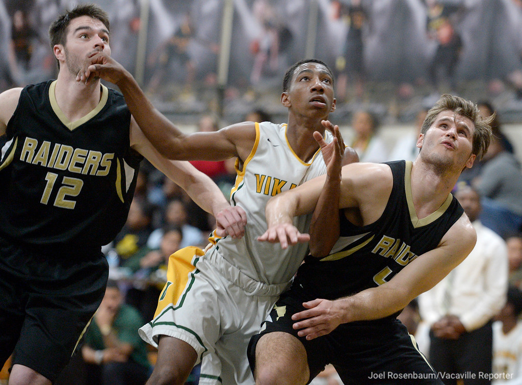 . Vanden\'s Marquis Davison-Holloway (middle) battles underneath the boards for position with Rio Americano\'s Matt Dixon (left) and Mitchell Dixon during a free throw attempt during the fourth quarter of their upset loss in the quarterfinals of the 2018 CIF Sac Joaquin Section Division IV Championships Friday at James Boyd Gymnasium.