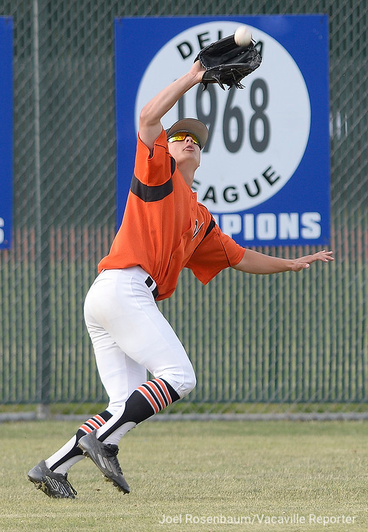 . Vacaville High\'s George Christison tracks down a fly ball in deep left field during the third inning of the Bulldogs victory.