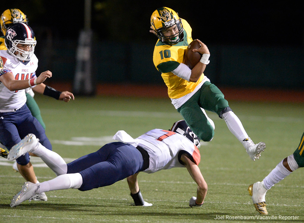 . Vanden High quarterback, Jonathan Brenes leaps over Rancho Cotate linebacker, Anthony Scardina as he runs for big gain during early in the third quarter.