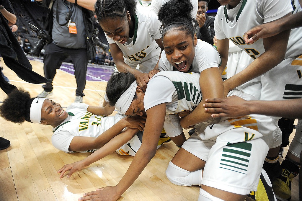 . Vanden�s Julia Blackshell-Fair is mobbed by her teammates as they celebrate their 64-61 victory over Mater Dei High School in the CIF Girls Division II State Championship Saturday at the Golden 1 Center in Sacramento.Joel Rosenbaum -- The Reporter