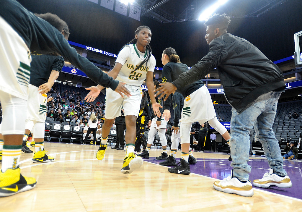 . Vanden\'s Deirdre Huff slaps hands with her teammates during player introductions before tip off of the Vikings\' CIF Girls Division II State Championships against Mater Dei High School Saturday at the Golden 1 Center in Sacramento. Joel Rosenbaum -- The Reporter