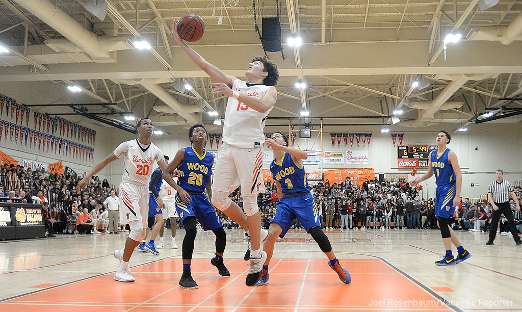 . Vaca High\'s Joey Murga pulls down an offensive rebound in front of Wood\'s Ricky Holland (20) and Tyreese Carson during the second quarter.