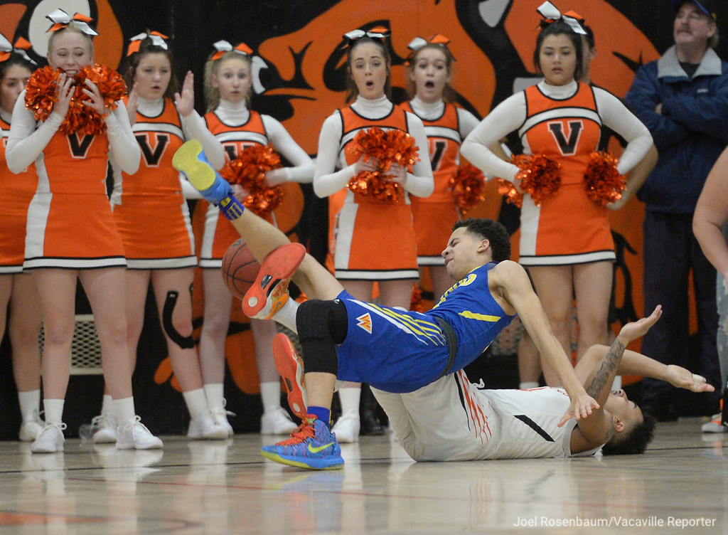 . Will C. Wood\'s Tyreese Carson and Issac Zulueta fall to floor after they collided while chasing after a loose ball during the first quarter.