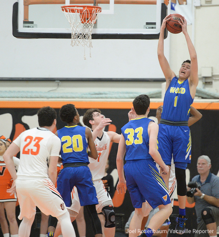. Wood\'s Jay Nagle pulls down a defensive rebound during the first quarter of the Wildcats 49-47 loss to their cross-town rivals, Vacaville High Friday at Harold Youngblood Gymnasium.