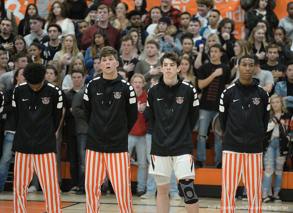 . Members of the Vaca High basketball team stand as the national anthem is sung before tip off of their first place showdown with cross-town rival Will C. Wood.