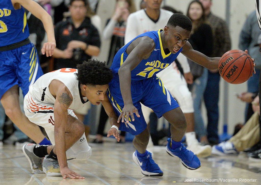 . Wood\'s Jeremiah Jones works to regain his balance after recovering a loose ball in front of Vaca High\'s Johnathan Tubbs during the third quarter.