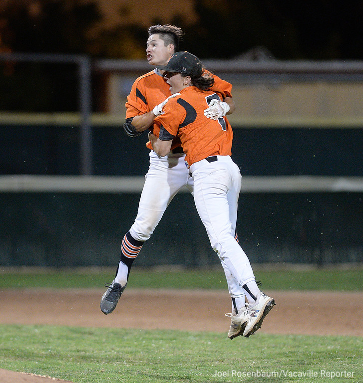 . Vaca High\'s George Christison (left) and Devereaux Harrison leap into air as they celebrate their 7-6 victory over Davis High School to win the 2018 CIF Sac-Joaquin Section Division I Championships Monday in Sacramento. Christison\'s bunt in the bottom of the seventh inning brought home the winning run with two outs