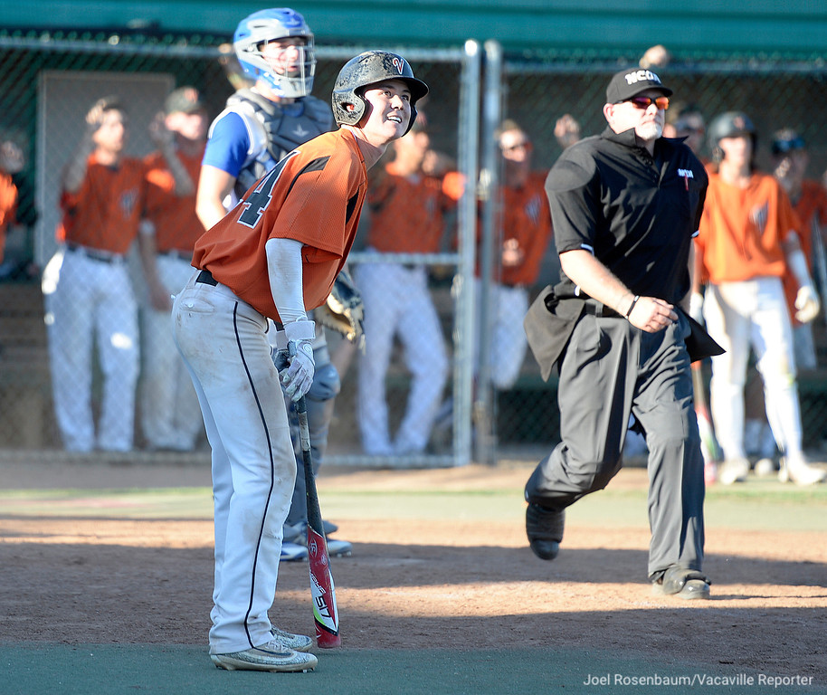 . Vacaville High School\'s Bryce Begell watches and waits for his fly ball to drop fair or foul during the fifth inning of the Bulldogs 11-4 victory in the first game of the two game showdown over Davis High School Monday at Sacramento City College.