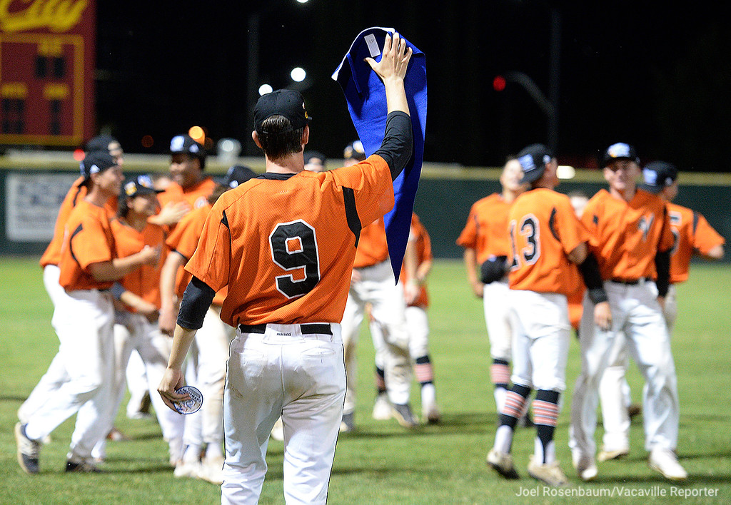 . Vaca High\'s TJ Smith holds the Section Championship banner for his teammates during the postgame celebration. Smith hit his first home run in his high school career to tie the ball game in the bottom of the seventh inning.