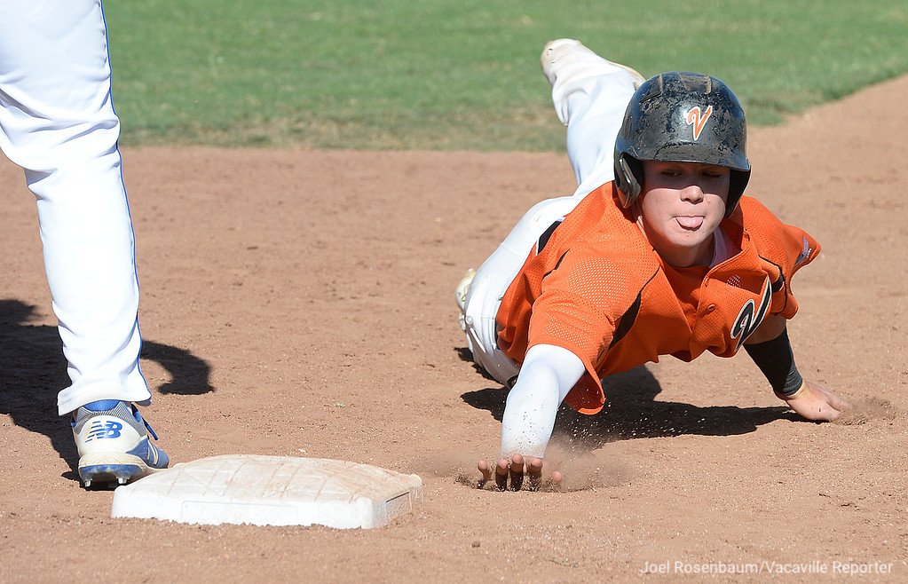 . Vacaville High\'s Bryce Begell dives back safely to first base on a pick off attempt in the third inning of the Bulldogs 11-4 victory in game one of their two-game showdown with Davis High School in the 2018 CIF Sac-Joaquin Section Division I Championship at Sacramento City College.