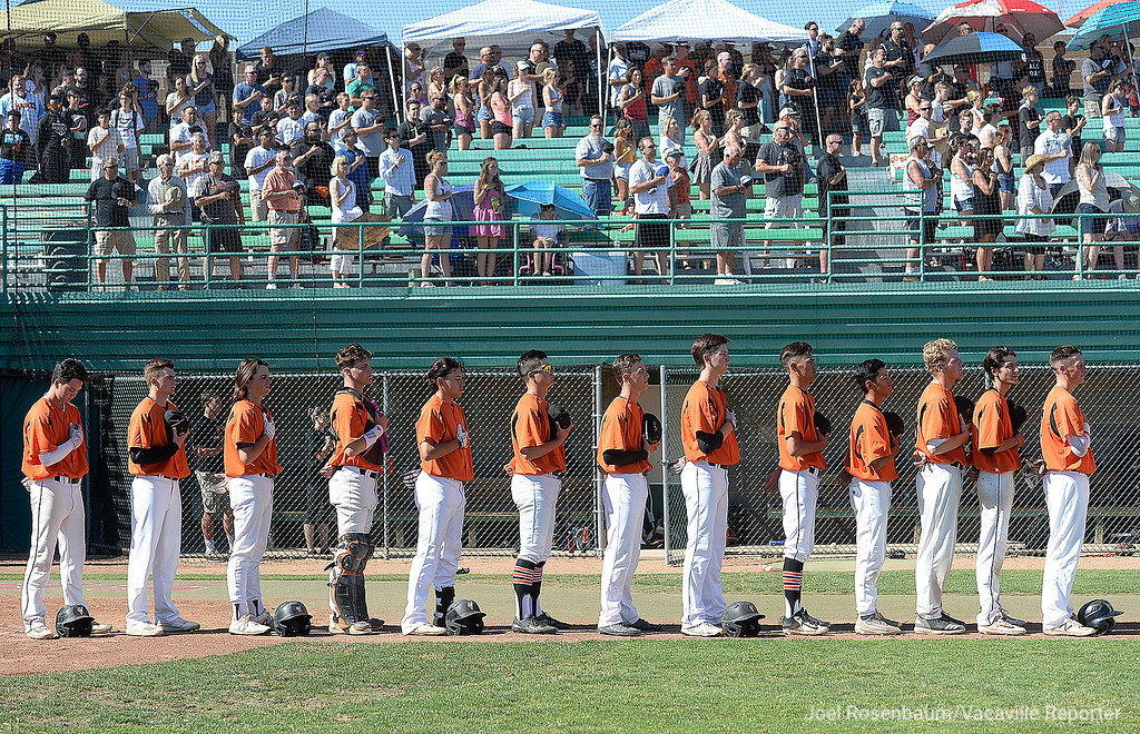 . Members of the Vacaville High School baseball team stand along the third baseline as the national anthem is played before the start of game one of their two-game showdown with Davis High School in the 2018 CIF Sac-Joaquin Section Division I Championship at Sacramento City College.