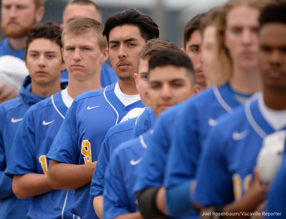 . Will C. Wood baseball players stand along the third baseline as the national anthem is played before their game against their cross-town rival, Vacaville High School Thursday at Wood.