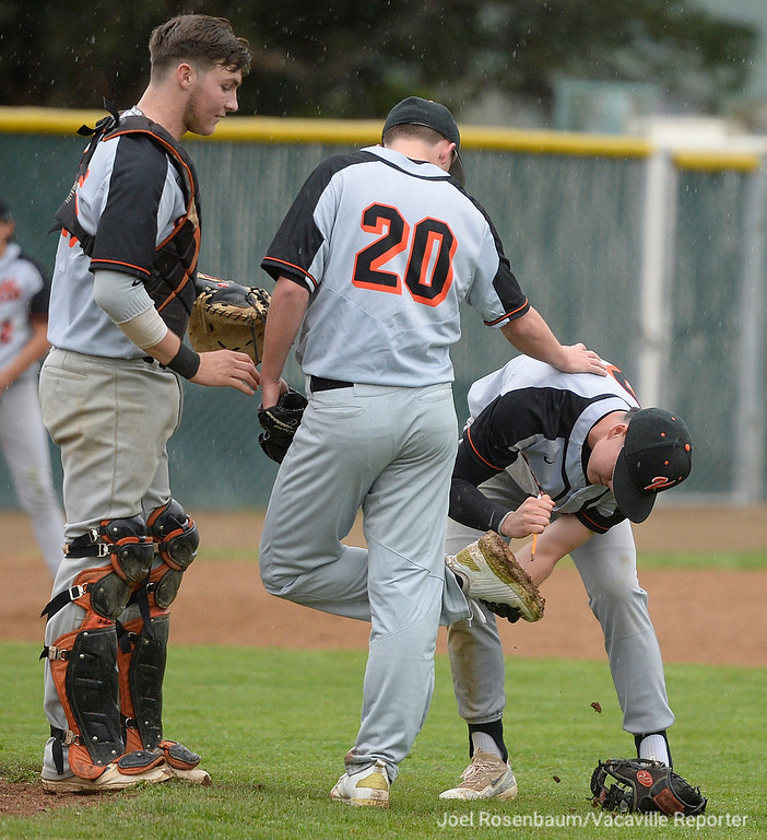 . Vaca High shortstop, Bryce Begell helps scrape mud from the cleats of teammate Brandon Chalk during the seventh inning.