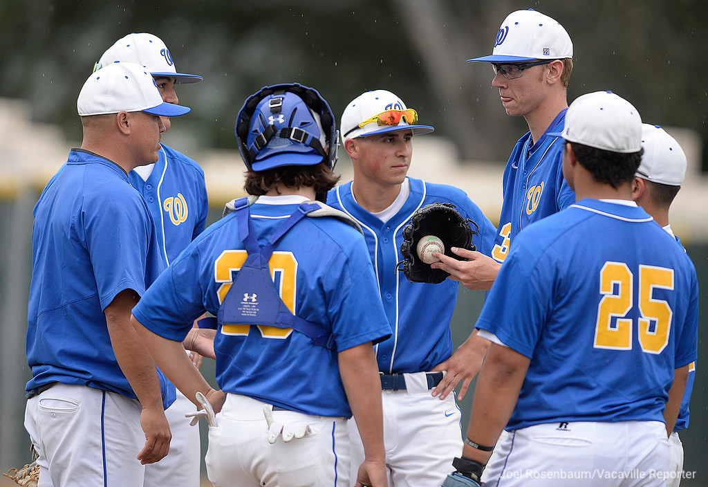 . Will C. Wood head coach, Nick Voight (second from left) meets with his players during a break in the action in the fourth inning.