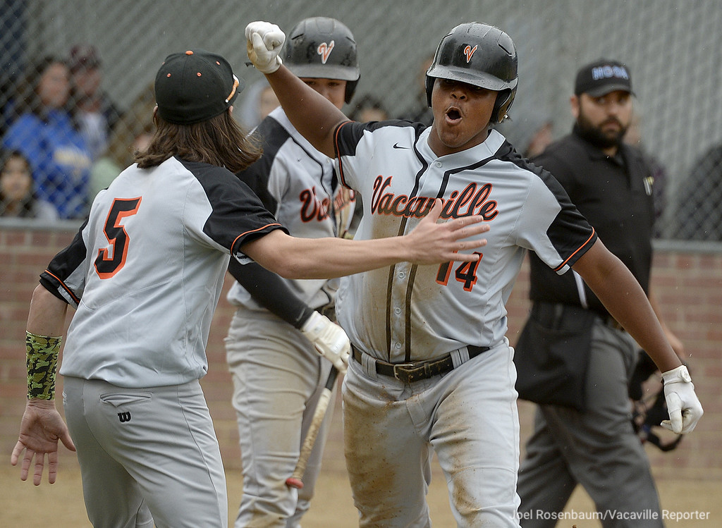 . Vacaville High\'s Michael Brown celebrates scoring the Bulldogs\' first run of game  in the fourth inning with teammate Devereaux Harrison of the  Bulldogs 5-2 victory over their cross-town rival, WIll C. Wood Thursday at Wood. Brown also broke up Wood pitcher, Titus Groeneweg\'s no-hitter in the inning.