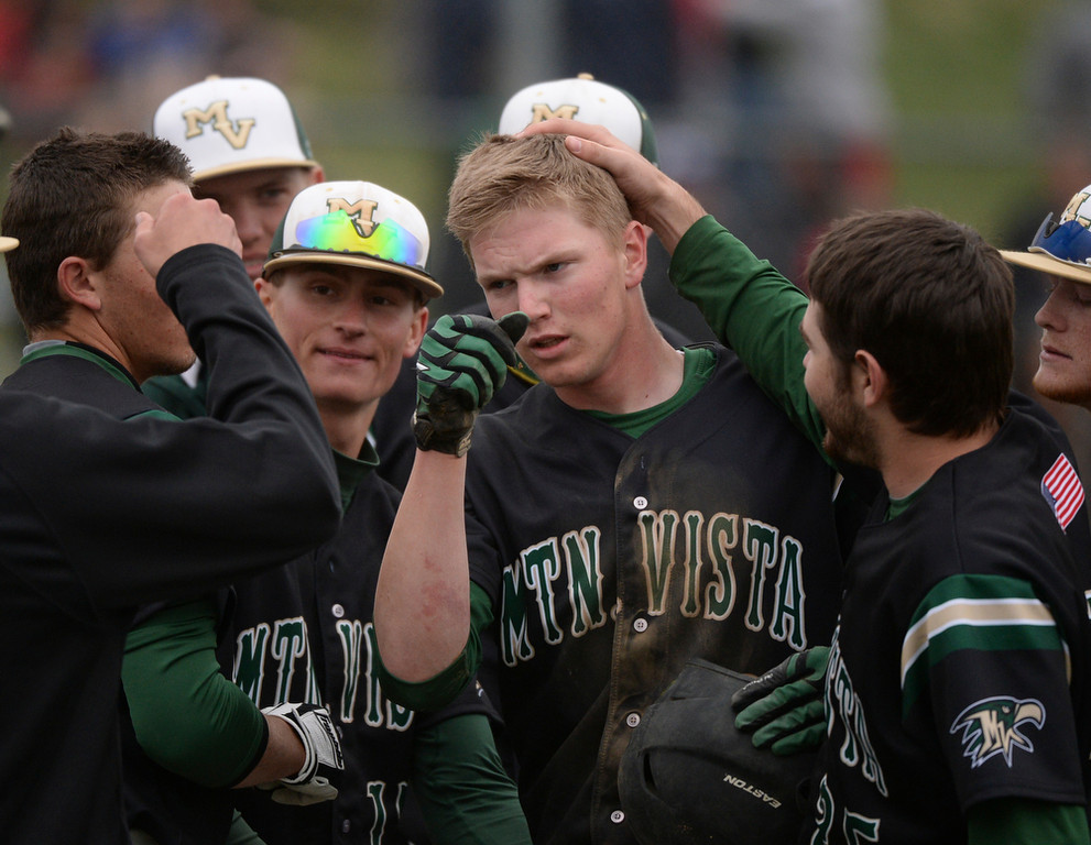 . Golden Eagles senior Michael Dunnebecke (10) celebrated with teammates after he drove in three runs with a triple in the sixth inning. The Mountain Vista High School baseball team blanked ThunderRidge 3-0 Wednesday afternoon, April 16, 2014. (Photo by Karl Gehring/The Denver Post)