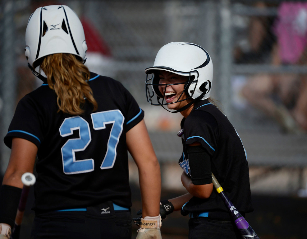 . Mountain Range High School softball players, Kaylee Dethouars, right, and Riley Craig, left, have laugh with each other during the championship game against Westminster High School of the inaugural 2014 King of the Mountain 5A softball tournament at Mountain Range High School Saturday afternoon, August 30, 2014. (Photo By Andy Cross / The Denver Post)