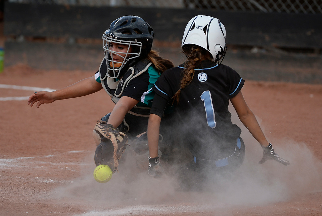 . Mountain Range High School softball player, Kaylee Dethouars, right, beats the throw to home and scores against Westminster catcher, Angel Abeyta, in the 6th inning during the championship game of the inaugural 2014 King of the Mountain 5A softball tournament at Mountain Range High School Saturday afternoon, August 30, 2014. Mountain Range won 15-2. (Photo By Andy Cross / The Denver Post)