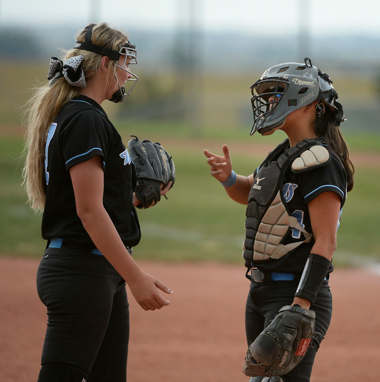 . Mountain Range High School pitcher, Hunter Huser, left, and catcher, Valerie Ortega, have a discussion at the mound against Westminster during the championship game of the inaugural 2014 King of the Mountain 5A softball tournament at Mountain Range High School Saturday afternoon, August 30, 2014. (Photo By Andy Cross / The Denver Post)