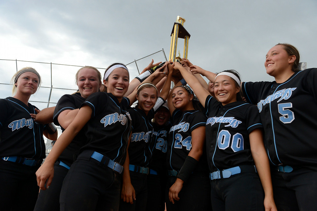 . The Mountain Range Mustangs celebrate their victory over the Westminster Wolves after winning  the inaugural 2014 King of the Mountain 5A softball tournament at Mountain Range High School Saturday afternoon, August 30, 2014. The Mustangs won 15-2. (Photo By Andy Cross / The Denver Post)