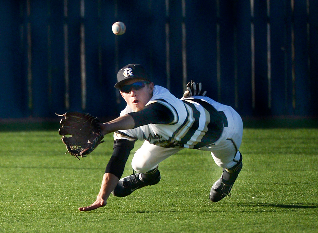 . Rock Canyon left-fielder Trevor Howard made a diving catch to rob Regis batter Max George of a hit in the seventh inning. The Regis Jesuit baseball team defeated Rock Canyon 10-1 Friday afternoon, April 11, 2014.  (Photo by Karl Gehring/The Denver Post)