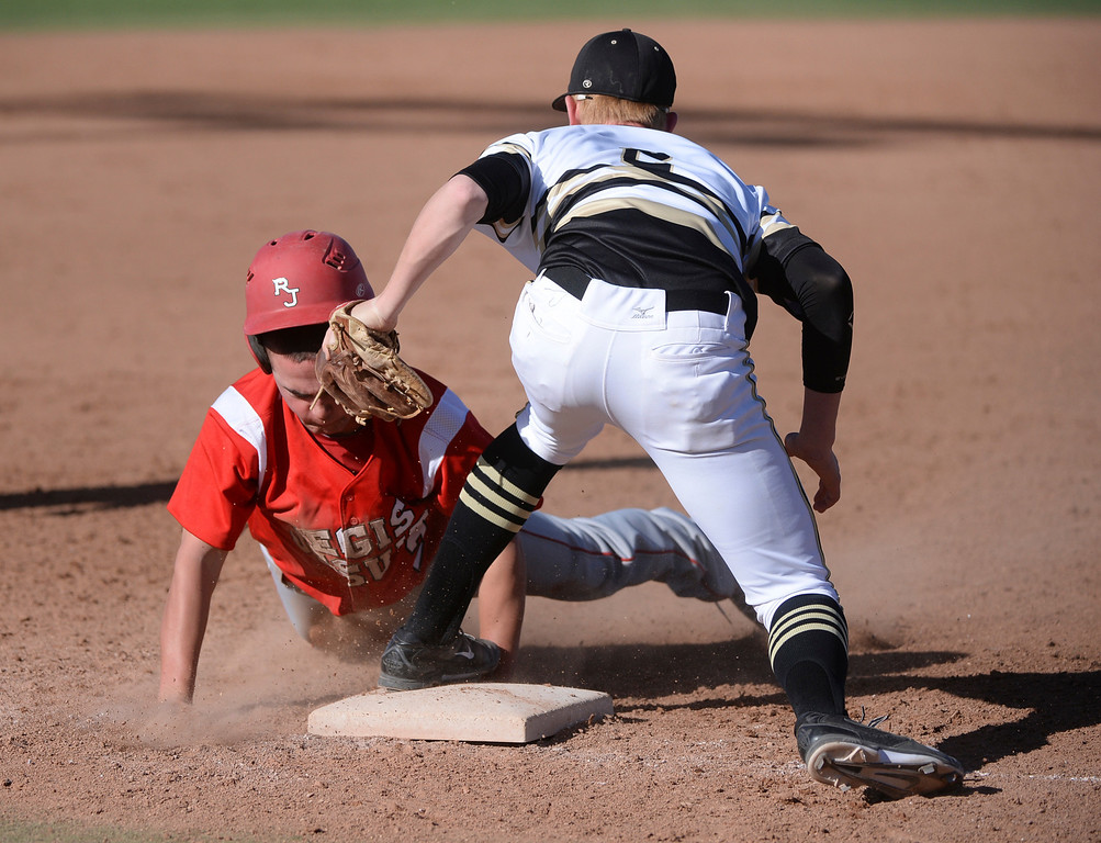 . Regis baserunner  Ryan Vottiero, left, advanced safely to third base in the third inning before Rock Canyon infielder Logan Hefflebower could apply the tag. The Regis Jesuit baseball team defeated Rock Canyon 10-1 Friday afternoon, April 11, 2014.  (Photo by Karl Gehring/The Denver Post)