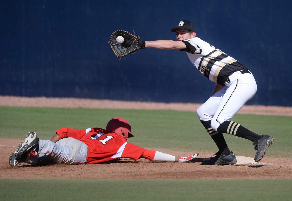 . Regis baserunner Quinn Cotton dived back to the bag as Rock Canyon first baseman Ben Sneider took the attempted pick off throw from the pitcher in the first inning. The Regis Jesuit baseball team defeated Rock Canyon 10-1 Friday afternoon, April 11, 2014.  (Photo by Karl Gehring/The Denver Post)