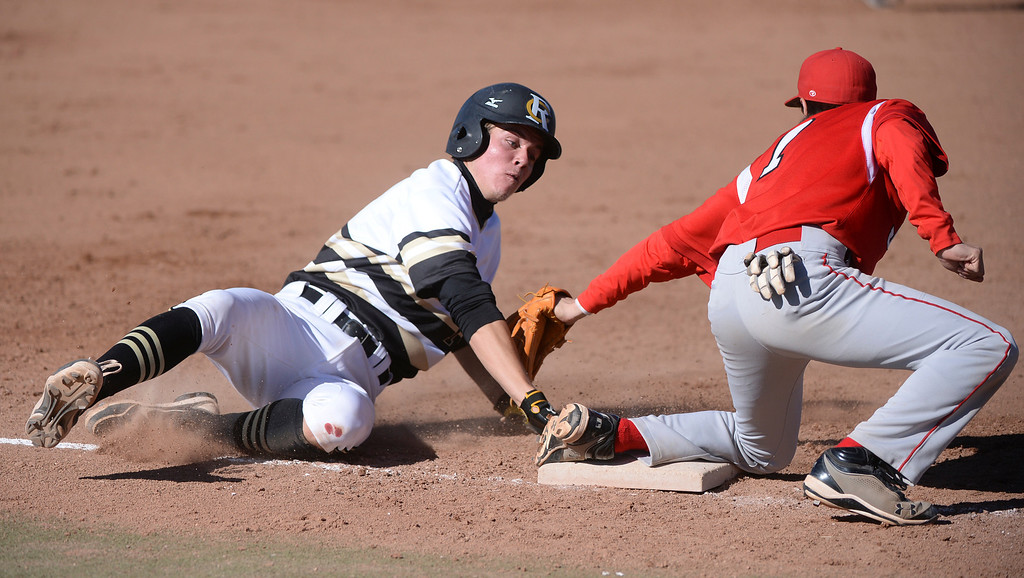. Rock Canyon baserunner Chris Given slid safely into third with a stolen base as Regis infielder Anthony Donovan reached to make the tag in the first inning. The Regis Jesuit baseball team defeated Rock Canyon 10-1 Friday afternoon, April 11, 2014.  (Photo by Karl Gehring/The Denver Post)